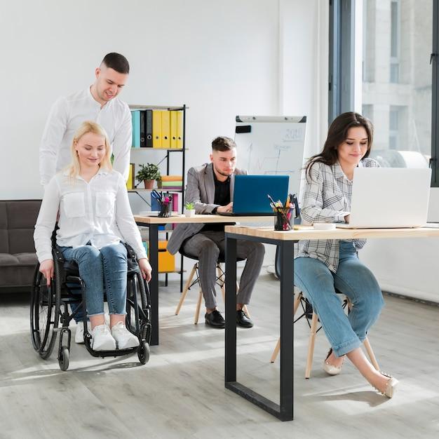 Vista frontal de la mujer en silla de ruedas ayudada por un compañero de trabajo en la oficina Foto gratis