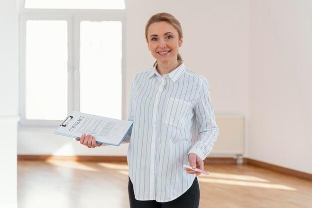 Vista frontal de la mujer sonriente agente de bienes raíces en casa vacía con portapapeles Foto gratis
