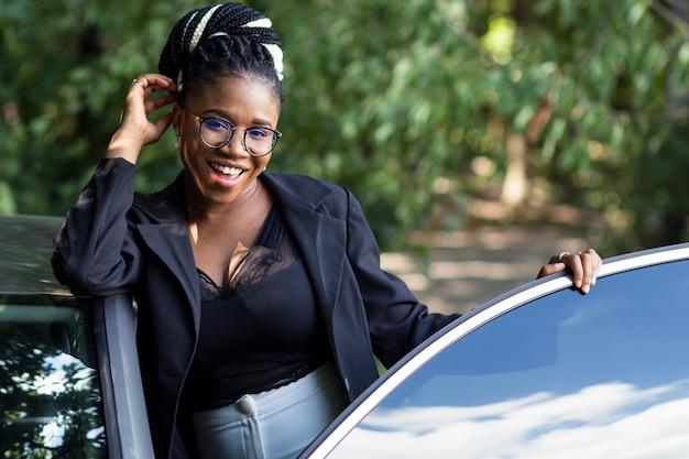 Vista frontal de la mujer sonriente posando con su coche nuevo Foto gratis