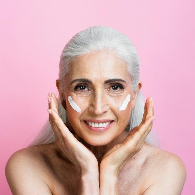 Vista frontal mujer sonriente con producto para el cuidado de la piel Foto gratis