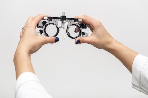 Vista frontal de la mujer sosteniendo equipos ópticos Foto gratis
