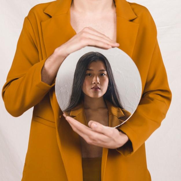 Vista frontal de una mujer sosteniendo un espejo redondo con su cara. Foto gratis