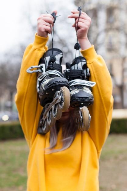 Vista frontal de la mujer sosteniendo patines Foto gratis