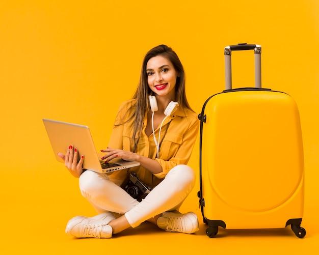 Vista frontal de la mujer sosteniendo portátil y posando junto al equipaje Foto gratis