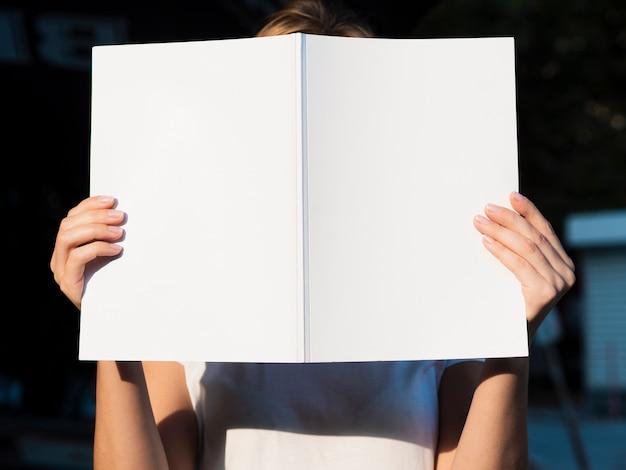 Vista frontal mujer sosteniendo una revista de maquetas Foto gratis