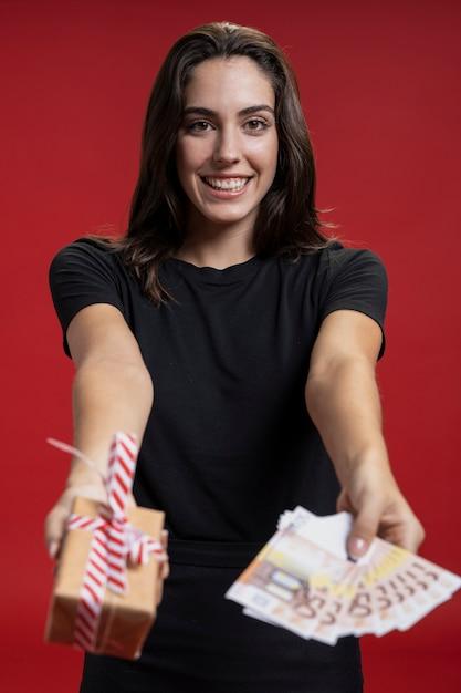 Vista frontal mujer con tarjetas de crédito y regalo Foto gratis