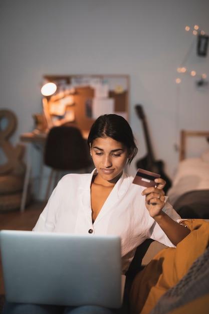 Vista frontal mujer trabajando en la computadora portátil y sosteniendo una tarjeta Foto gratis