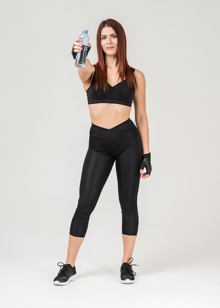 Vista frontal de la mujer en traje de gimnasio posando mientras sostiene una botella de agua Foto gratis