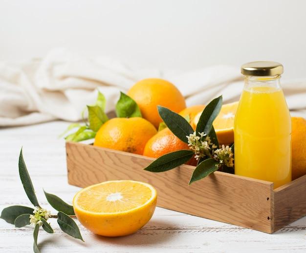 Vista frontal de naranjas y jugo en caja de madera. Foto gratis