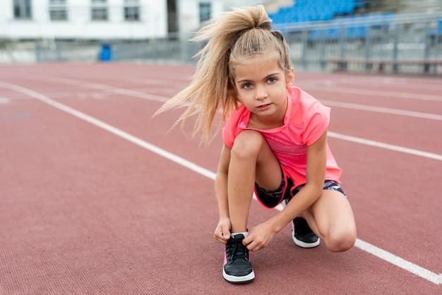 Vista frontal de la niña atando sus cordones Foto gratis