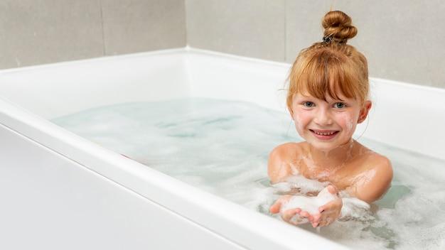 Vista frontal niña en la bañera Foto gratis