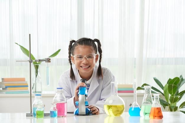 Vista frontal de la niña en bata de laboratorio haciendo el experimento químico Foto gratis