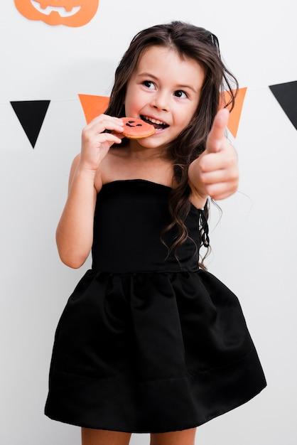 Vista frontal niña comiendo una galleta Foto gratis