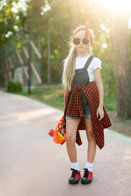 Vista frontal de niña con gafas de sol Foto gratis
