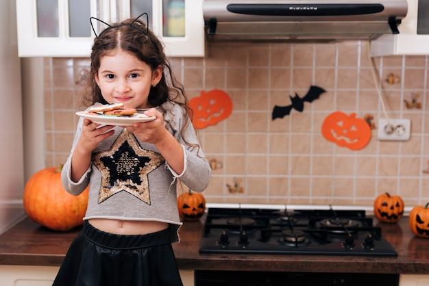 Vista frontal de una niña con un plato de galletas Foto gratis