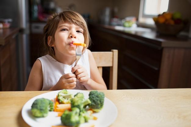 Vista frontal de la niña que tiene verduras Foto gratis