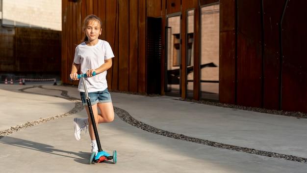 Vista frontal de la niña con scooter azul Foto gratis