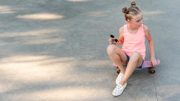 Vista frontal de la niña sentada en patineta Foto gratis