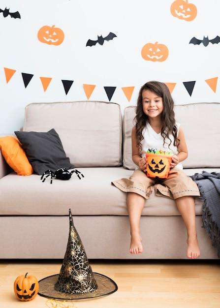 Vista frontal niña sentada en el sofá en halloween Foto gratis