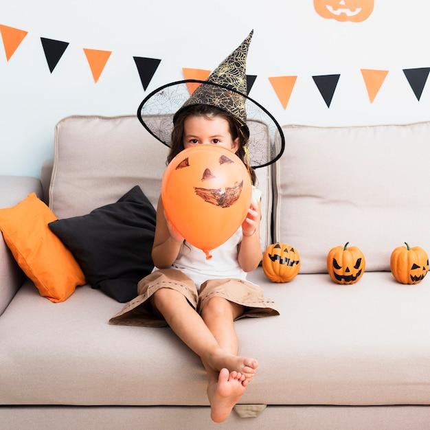Vista frontal niña sosteniendo un globo de halloween Foto gratis