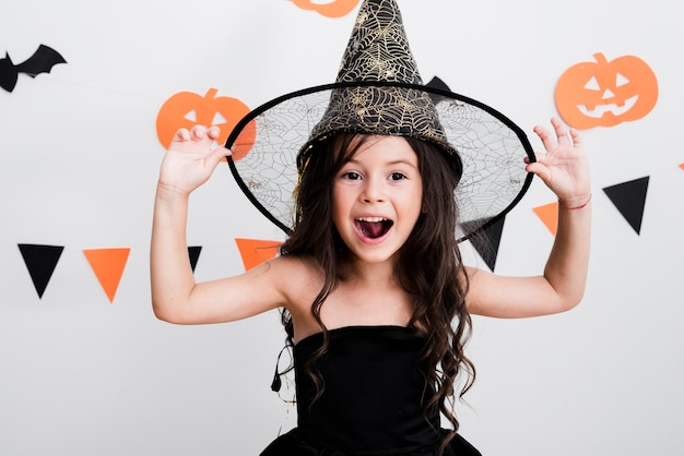 Vista frontal niña en traje de bruja para halloween Foto gratis
