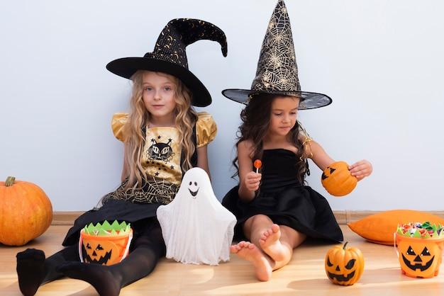 Vista frontal niñas sentadas en el piso en halloween Foto gratis