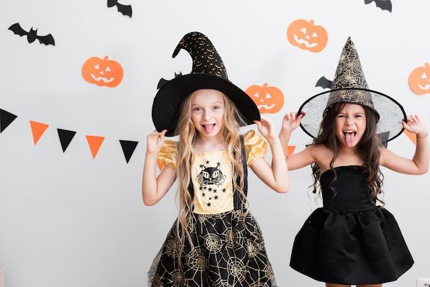 Vista frontal de niñas en traje de bruja para halloween Foto gratis