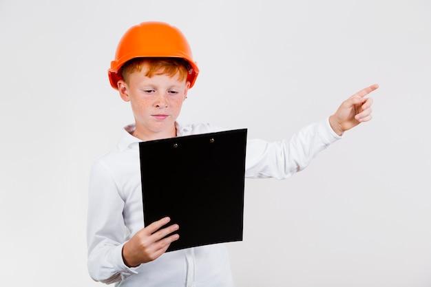 Vista frontal niño haciéndose pasar por trabajador de la construcción Foto gratis