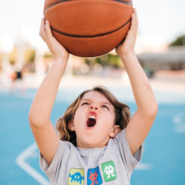 Vista frontal del niño jugando baloncesto Foto gratis