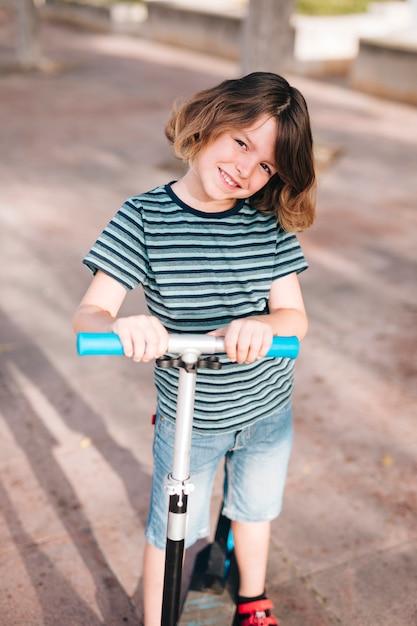 Vista frontal del niño con scooter Foto gratis