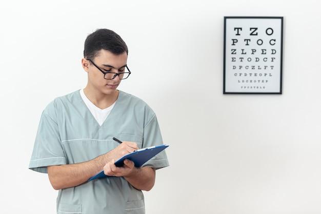 Vista frontal del oftalmólogo con bloc de notas y escritura Foto gratis
