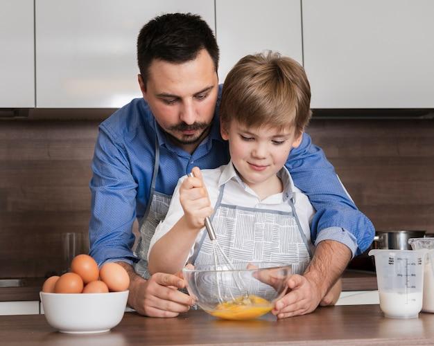 Vista frontal padre e hijo mezclando huevos Foto gratis