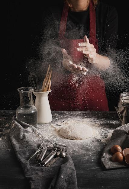 Vista frontal panadero limpiando las manos de harina Foto gratis