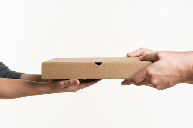 Vista frontal de un par de manos sosteniendo la caja de pizza Foto gratis