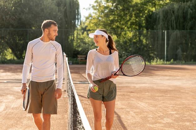 Vista frontal pareja en cancha de tenis Foto gratis