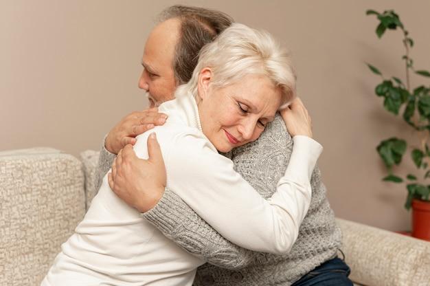 Vista frontal pareja senior en sofá abrazando Foto gratis