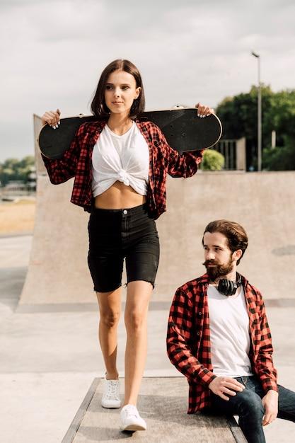 Vista frontal de la pareja en el skate park Foto gratis