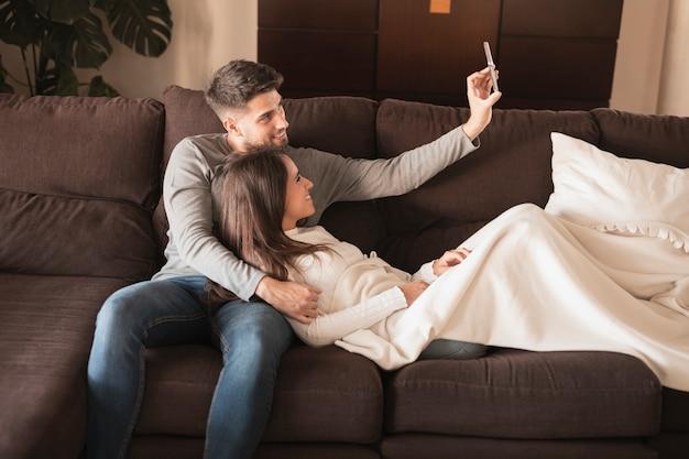 Vista frontal pareja en el sofá tomando selfie Foto gratis
