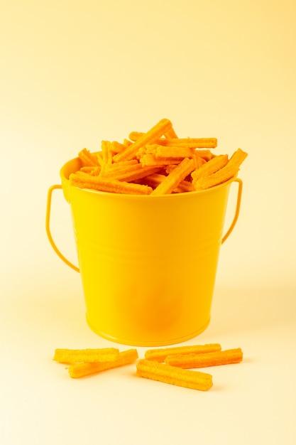 Una vista frontal de pasta dentro de la cesta formada naranja cruda dentro de la cesta amarilla sobre el fondo crema comida comida pasta Foto gratis