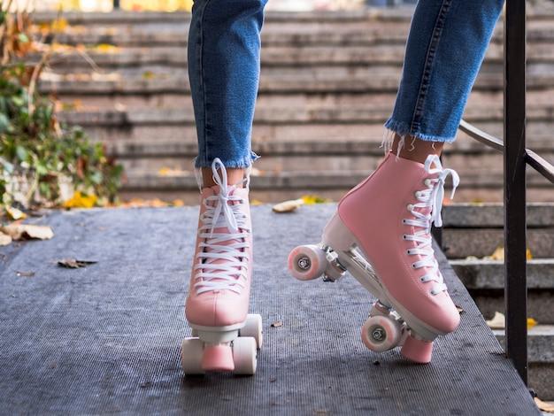 Vista frontal de patines sobre mujer en jeans Foto gratis