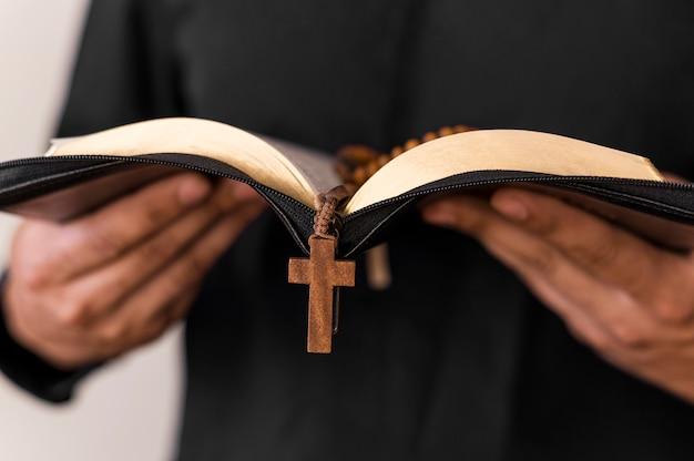 Vista frontal de la persona con libro sagrado y rosario Foto gratis