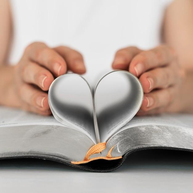 Vista frontal de la persona que hace el corazón de las páginas del libro sagrado Foto gratis