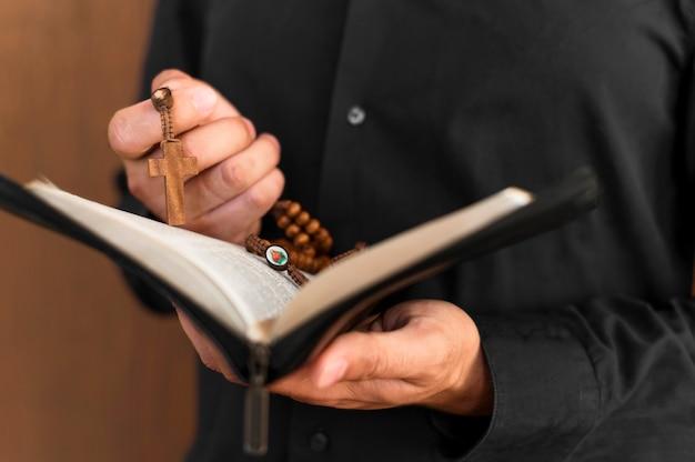 Vista frontal de la persona que sostiene el libro sagrado y el rosario Foto gratis