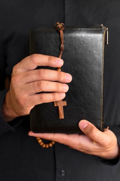 Vista frontal de la persona que sostiene el libro sagrado con rosario Foto gratis