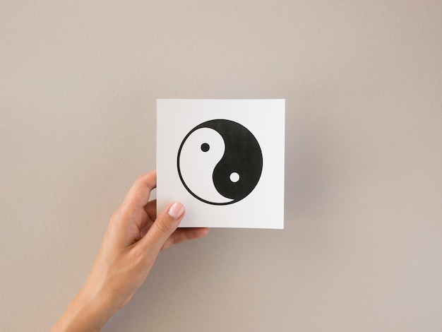 Vista frontal de la persona que sostiene el símbolo ying y yang Foto gratis