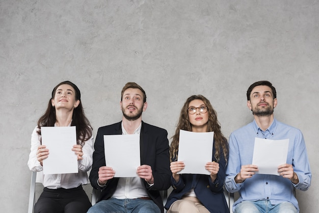 Vista frontal de las personas que esperan sus entrevistas de trabajo con papeles en blanco con espacio de copia Foto gratis