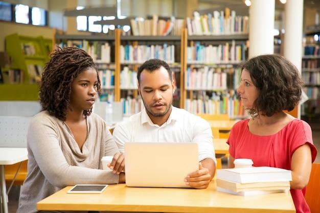 Vista frontal de personas reflexivas que trabajan en la biblioteca Foto gratis
