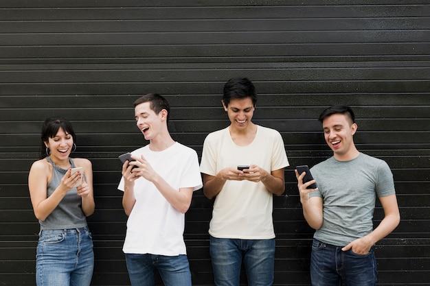 Vista frontal de personas con teléfonos móviles Foto gratis
