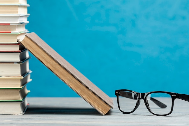 Vista frontal pila de libros con gafas Foto gratis