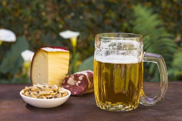 Vista frontal pinta con cerveza y aperitivos para beber Foto gratis